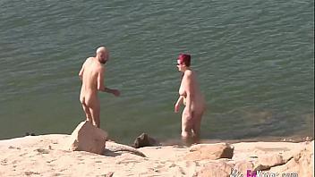 Pelirroja española tetona y su novio hacen un trío en la playa nudista